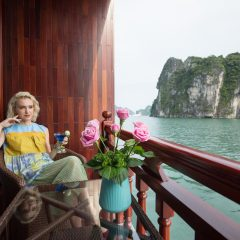 A lady sitting on the balcony of the ship overlooking Halong bay islands